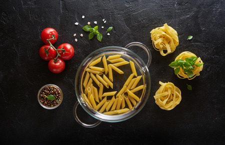 Different kinds of raw pasta with basil and tomatoes on black slate background. Top view.