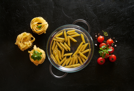 Raw pasta with basil and tomatoes on black slate background. Top view.