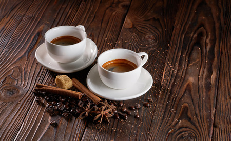 Two cups of espresso coffee on wooden table