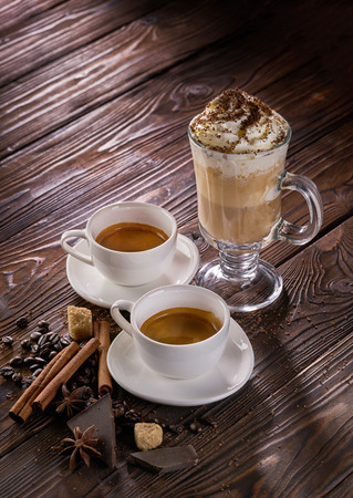 Two cups of freshly brewed espresso coffee and latte in a tall glass on wooden table