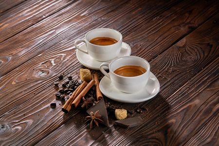 Two cups of freshly brewed espresso coffee with coffee beans on a rustic wooden table 免版税图像
