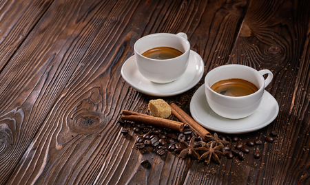 Two cups of freshly brewed espresso coffee with coffee beans on a rustic wooden table 写真素材
