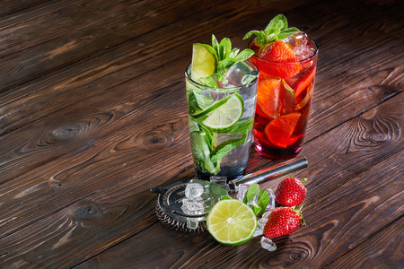 Mojito cocktails with lime, strawberry and mint in glass with ice cubes on wooden background