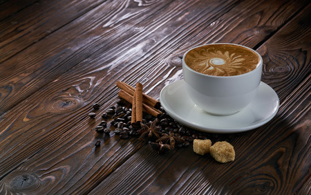 A cup of cappuccino with coffee beans, cinnamon and brown sugar on wooden table 写真素材