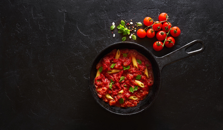 Penne pasta with tomato sauce and green basil decorated in a cast iron pan on a black background. Top view with copy space