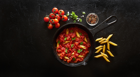 Cooking pasta penne with tomato sauce and basil served on iron cast pan. Black slate background, top view
