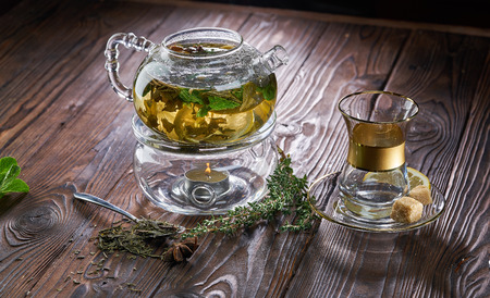 Teapot of herbal tea and fresh mint on wooden table