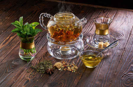 Teapot and cup of herbal tea with fresh mint flowers on wooden table