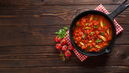 Homemade pasta penne with tomato sauce on wooden background