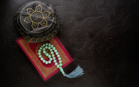 Islamic concept. Flat lay composition of holy book for muslim Quran, rosary beads and pray hat.