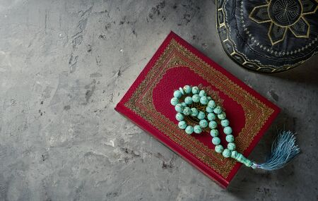 Islamic Book Koran with rosary and pray hat on grey slate background. Islamic concept with copy space