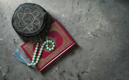 Islamic Book Koran with rosary and pray hat on grey slate background. Islamic concept with copy space, top view