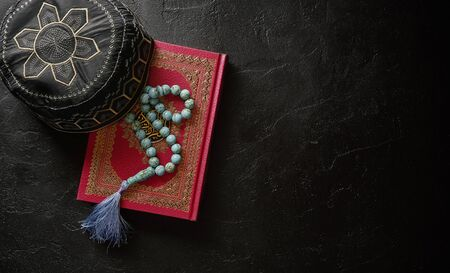 Koran with rosary and muslim hat on black stone or slate texture background. Islamic concept with copy space