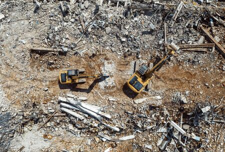 Excavators demolishing old factory for new construction project, aerial top view