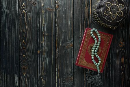 Islamic book Koran with rosary beads and pray hat on wooden background. Islamic concept with copy space Stock Photo