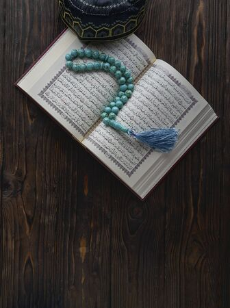 Open book Koran with rosary beads and muslim hat on wooden background. Islamic concept with copy space Stockfoto