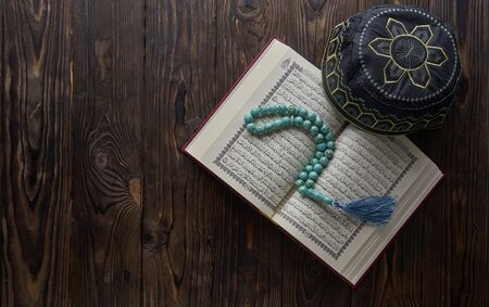 Islamic book Quran with rosary beads and muslim hat on wooden background. Islamic concept with copy space