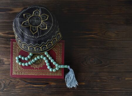 Islamic book Koran with rosary beads and muslim hat on wooden background. Islamic concept with copy space Stockfoto