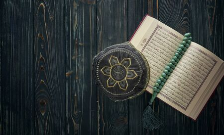 Open Koran with rosary beads and muslim hat on wooden background. Islamic concept with copy space
