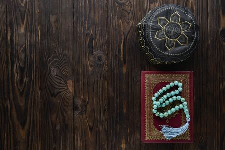 Koran with rosary beads and pray hat on wooden background. Islamic concept with copy space