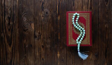 Islamic book Koran with rosary beads on wooden background. Islamic concept with copy space Stockfoto