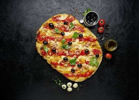 Top view of square pizza or pinsa with tuna on black slate background