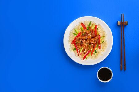 Stir-fry chicken meat, vegetables and rice on colorful background. Copy space, top view