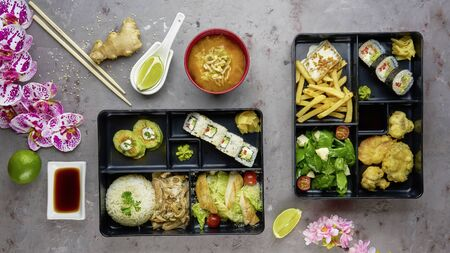 Japanese cuisine. lunch box set, sushi roll, salad, miso, chicken, sauce and wasabi on grey background.