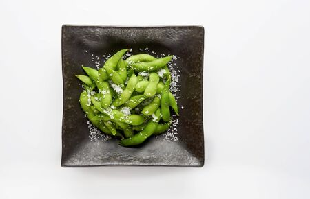 Edamame green soybeans in the bowl, fried green soybeans with salt in a black bowl on white background Stockfoto