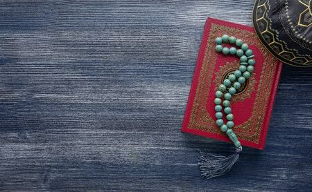 Islamic Koran with rosary beads on wooden background. Islamic concept with copy space