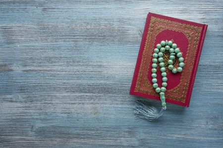 Islamic book Koran with rosary beads on wooden background. Islamic concept with copy space Stock Photo