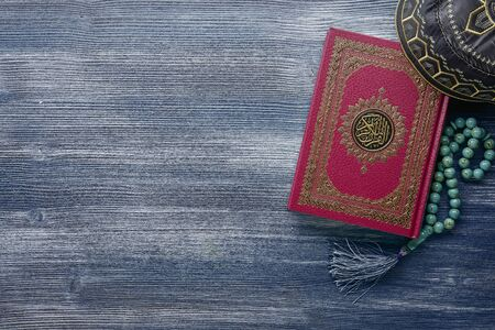 Koran with rosary beads on wooden background. Islamic concept with copy space