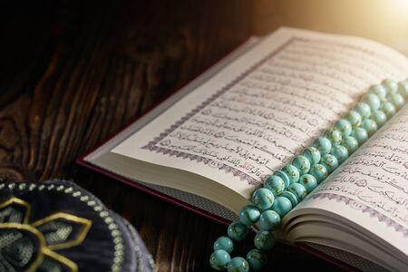 Islamischer Koran mit Rosenkranzperlen und Kopiah-Hut für Muslime auf Holztisch