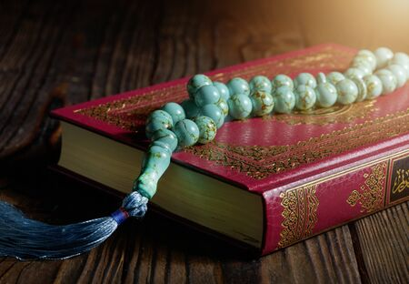 Islamic book Koran with rosary beads on wooden table Stockfoto