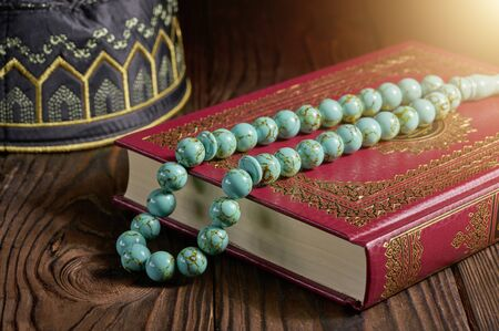 Quran book with rosary beads and kopiah hat for muslims on wooden table