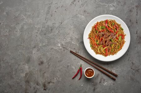 Soba noodles with beef and vegetables on grey stone background .Top view, copy space Stockfoto