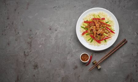 Stir-fry chicken meat, vegetables and rice on grey stone background. Copy space, top view