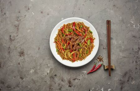 Noodles with beef and vegetables on grey stone background .Top view, copy space