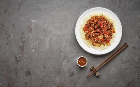 Sweet and Sour fried pork chunks with vegetables and rice on grey stone background. Top view with copy space