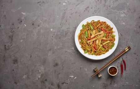 Chinese noodles with beef and vegetables on grey stone background .Top view, copy space