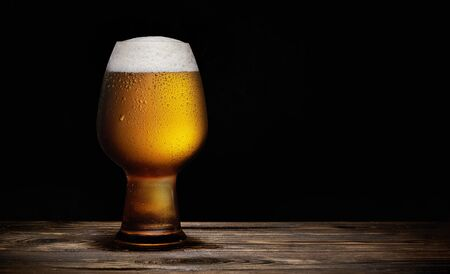 Glass of cold beer on a rustic wooden table Stockfoto