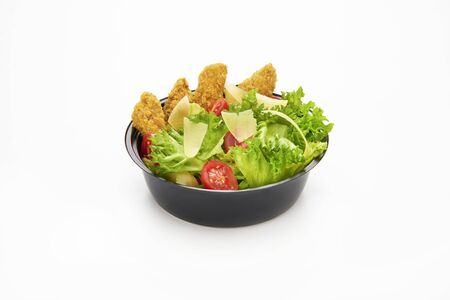 Salad with fried chicken strips and sliced parmesan cheese in a plastic take away bowl on white background Stock fotó