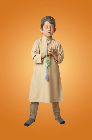 Little muslim boy praying and holding prayer beads on colorful background