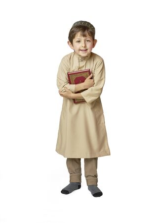 Happy muslim kid holding holy Quran on white background