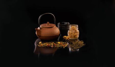 Chinese teapot and tea cups with tea leafs on black background Imagens
