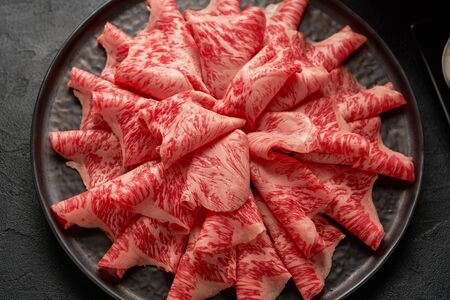 A close up detailed image of sliced Japanese wagyu beef in a ceramic plate prepared for Shabu Shab