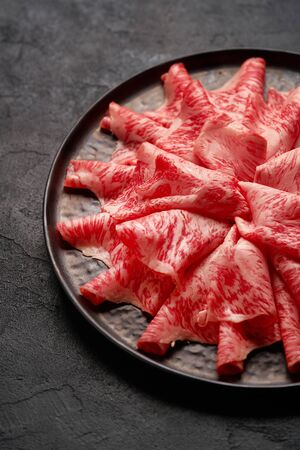 Japanese kobe beef sliced on ceramic plate on black background
