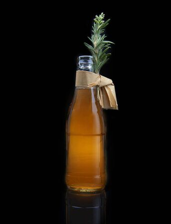 refreshing cocktail in bottle with rosemary, on black background