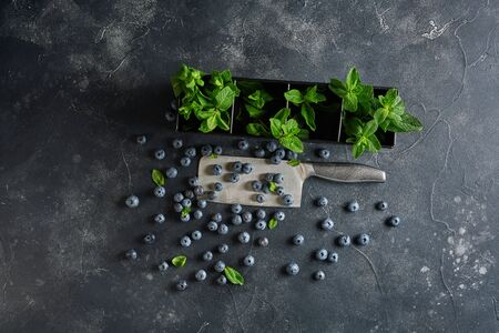 Top view of blueberries with fresh mint on dark rustic background with copy space.