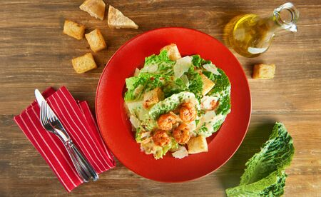 Fresh caesar salad on red plate with parmesan cheese and shrimps on wooden table. Top view Imagens